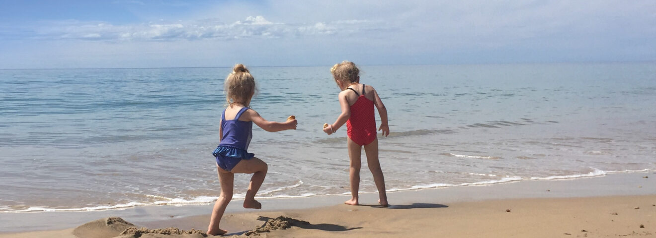 Two young girls playing on a beach