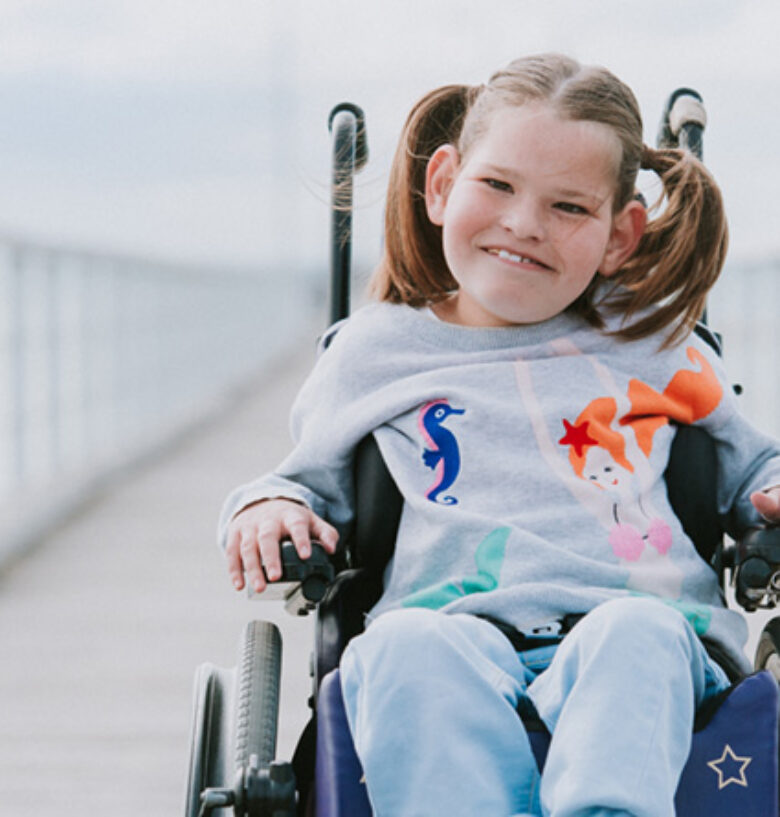 Young child named Allira, is sitting in a wheel chair on the jetty. She is wearing a mermaid top.