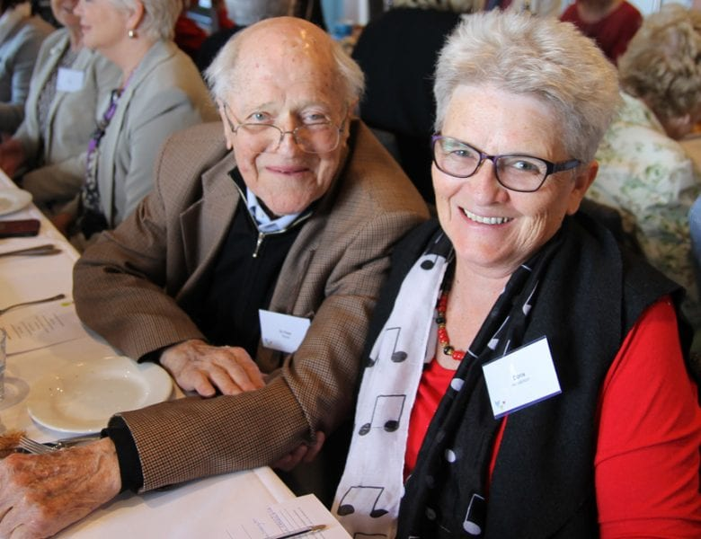 A man and woman sitting at a table at an event for the WCH Foundation.