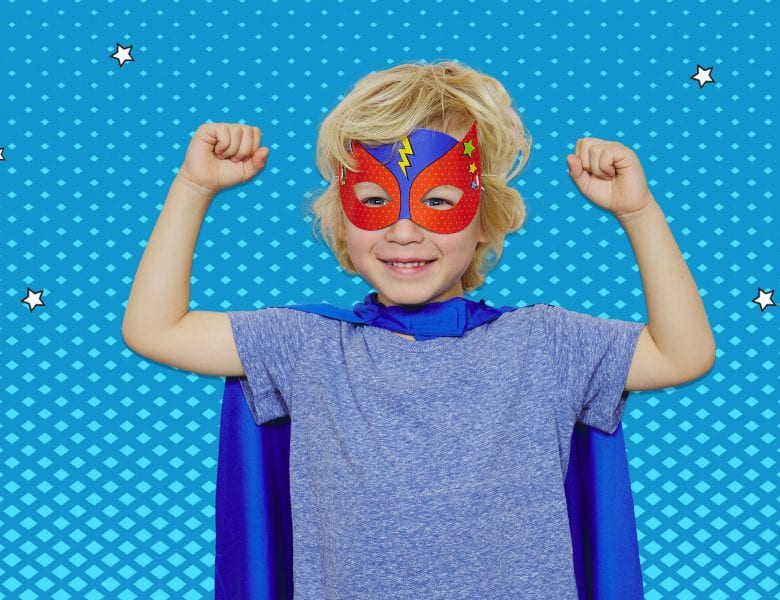 Young blonde boy smiling in superhero costume posing with fists up