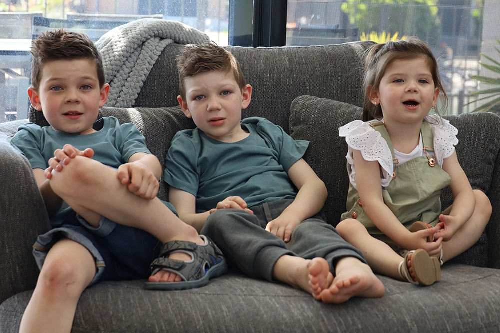 Two young brothers with their younger sister sitting on a couch smiling at the camera.