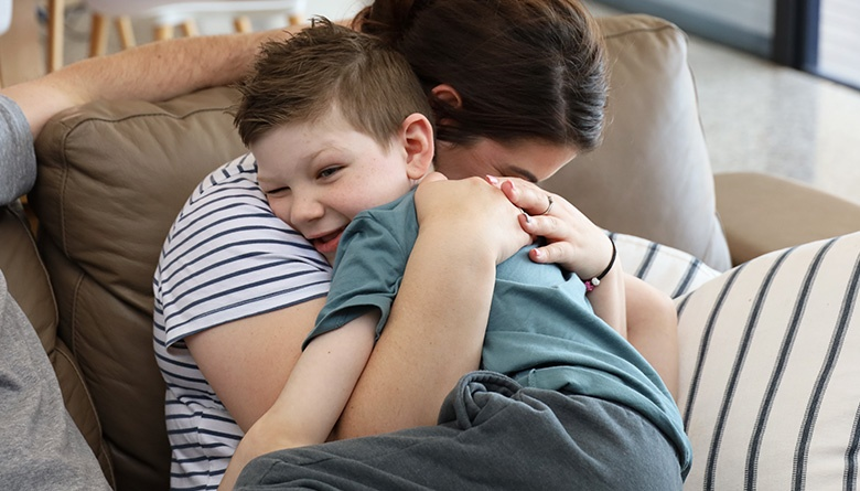 Young patient Declan in am embrace with his mum on a couch at the WCH Foundation Beach House.