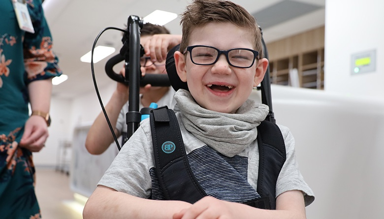 Young patient Declan in his wheelchair smiling at the camera being led by younger brother, Connor.