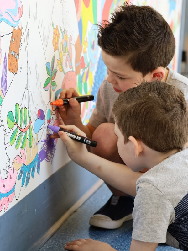 Young patients Declan and Connor colouring in a hospital mural.