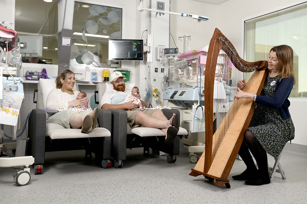 Babies and their parents in the neonatal nurseries listening to the harp.