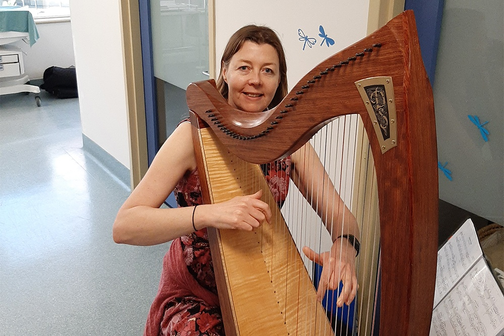 Ilona playing the harp in neonatal nurseries.